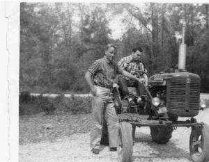 The young John Kennedy Toole attempts to shift gears on a tractor as his best friend, Cary Laird, poses for the camera.